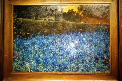 It seems as if Van Looy has lavishly strewn blue flowers all over this large canvas. Looking a bit longer, however, one notices the artist's house in Soest and the hay wagons behind the tall hedge, and in the right foreground an overturned pot among the flowers. The painter was clearly inspired by the landscapes of Van Gogh, but his representation of nature and the fall of light are more realistic.